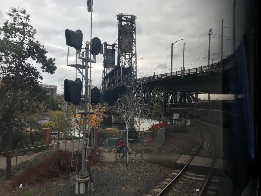 On the train traveling under regular car traffic on one of Portland's bridges